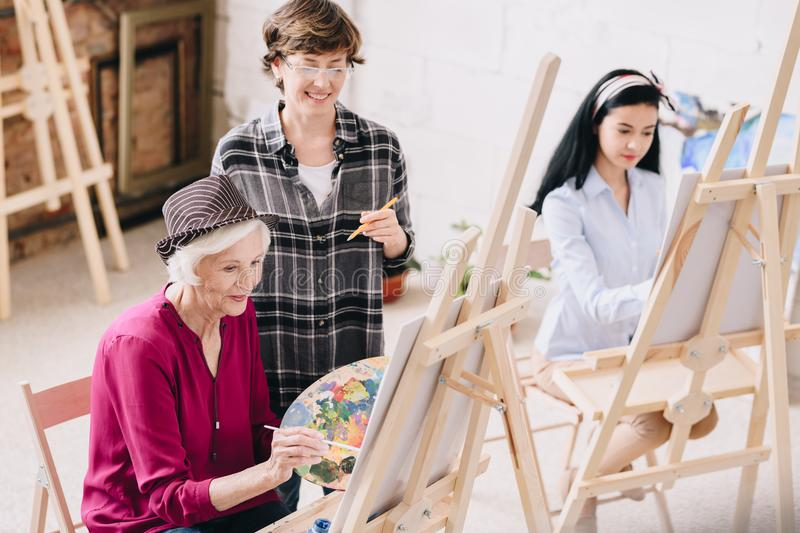 Female Art Teacher teaching Class. Portrait of elegant senior women painting sitting at easel in art studio with smiling female teacher giving comments, copy royalty free stock photos