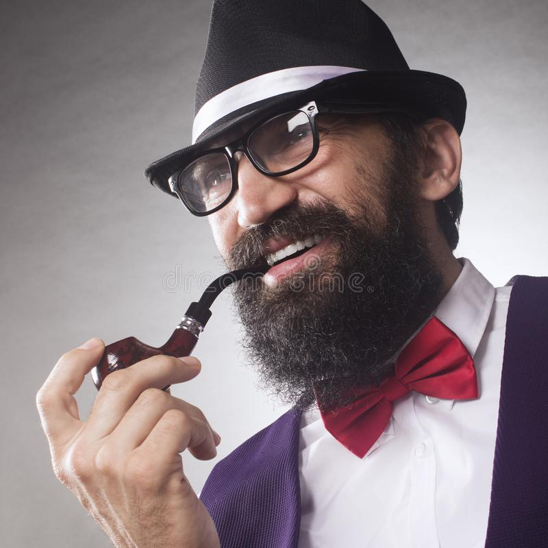 Bearded man smoking pipe. Portrait of elegant smiling bearded middle aged man with smoking pipe, eyeglasses and hat stock image