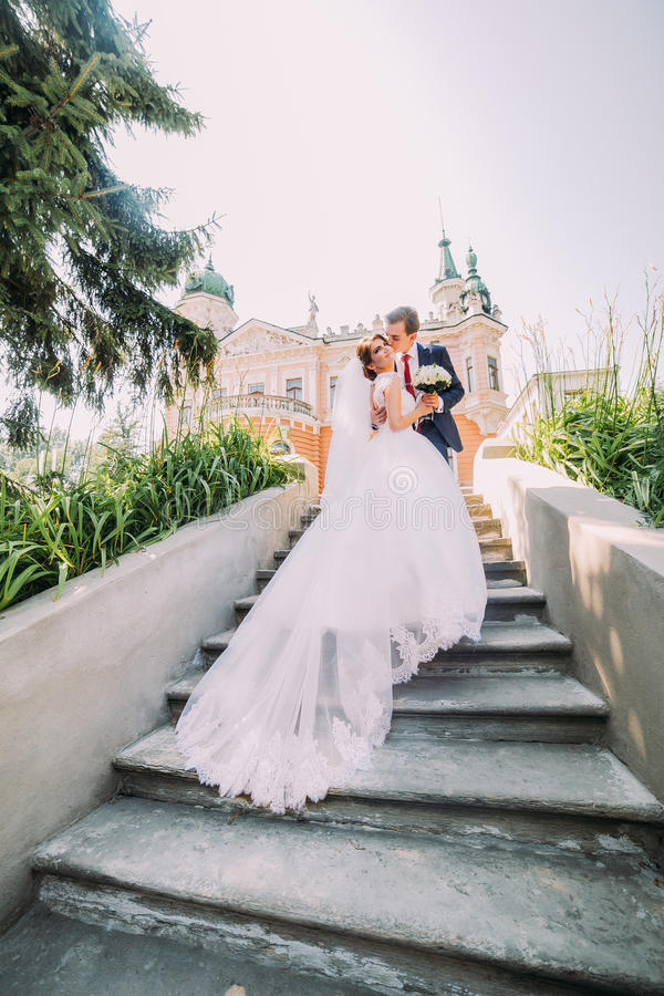 Portrait of elegant stylish young wedding couple on stairs in park. Groom is kissing his new wife, romantic antique palace at back stock photography