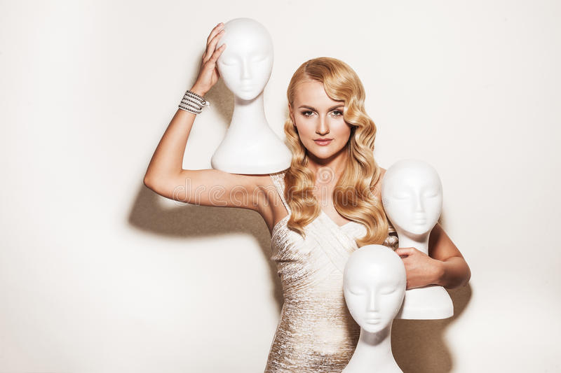 Portrait of elegant woman with mannequins. Beautiful blond woman with retro hairdo looking at camera. Luxury vogue style model holding white mannequins royalty free stock images