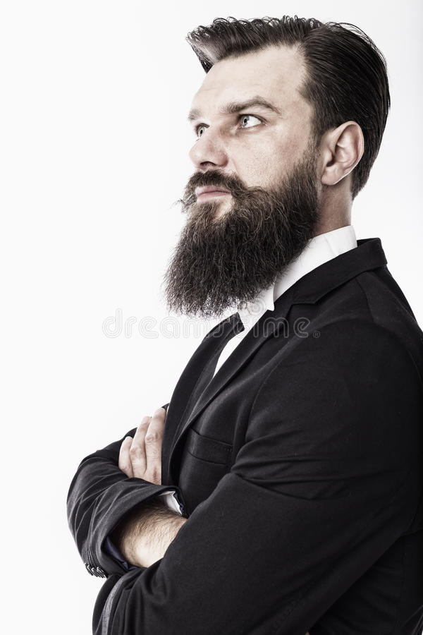 Portrait of an elegant young fashion man with beard and mustache. With arms folded over white royalty free stock photo