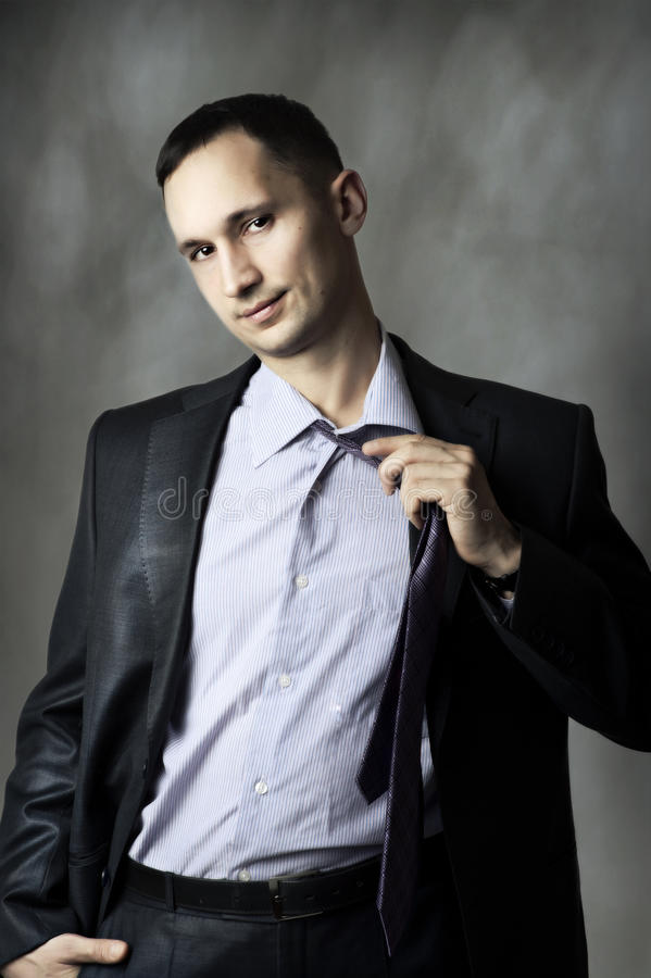 Portrait of the elegant young man. Untying a tie royalty free stock photo