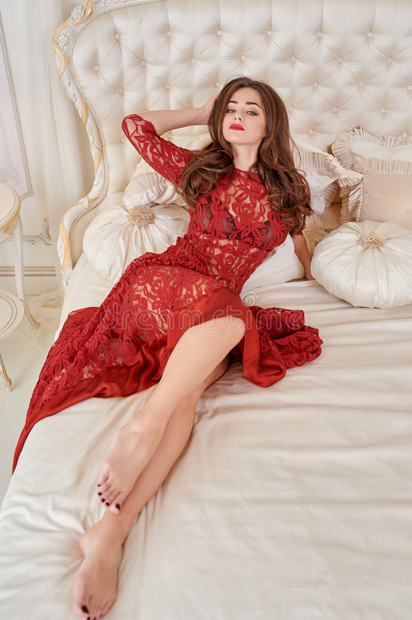 Portrait of elegant young woman in red dress on bed in a luxurious interior stock photography