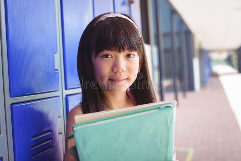 Portrait of elementary schoolgirl holding books in corridor stock photos