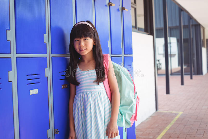 Portrait of elementary schoolgirl standing by lockers stock images