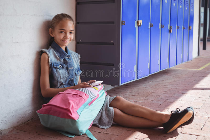 Portrait of elementary schoolgirl using mobile phone while sitting by lockers stock photo