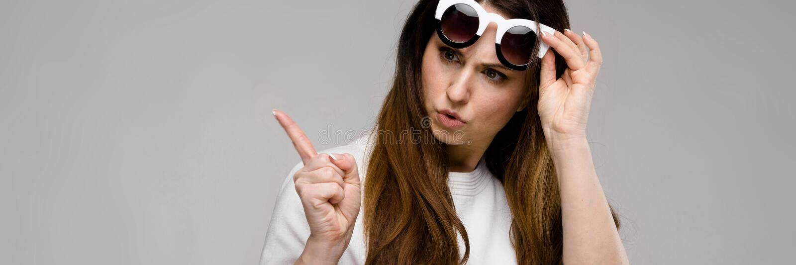 Portrait of emotional beautiful plus size model in sunglasses standing in studio looking in camera posing royalty free stock images