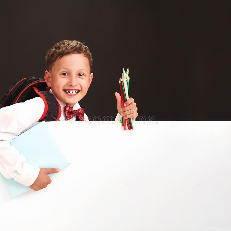 Portrait of an emotional child. boy-schoolboy smiles, happy to return to school. concepts about the student. holding white Banner royalty free stock image