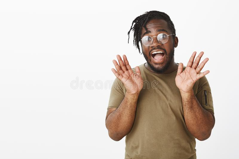 Portrait of emotional dark-skinned man with beard in glasses, smiling broadly and lifting palms near face, being amazed stock photos