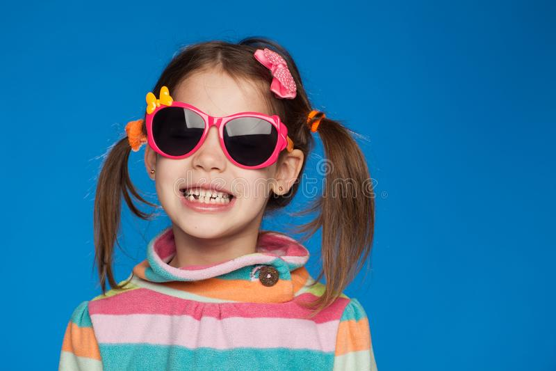 Portrait of an emotional girl of five years old in a striped sweater and in children`s glasses on a blue background stock image