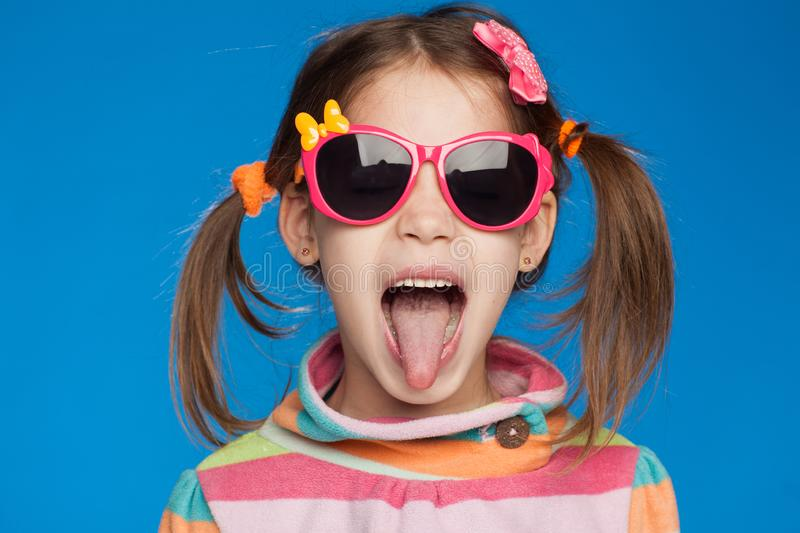 Portrait of an emotional girl of five years old in a striped sweater and in children`s glasses on a blue background stock photography