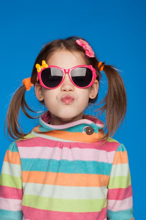 Portrait of an emotional girl of five years old in a striped sweater and in children`s glasses on a blue background royalty free stock image