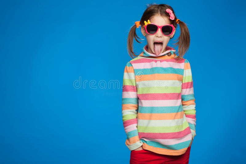 Portrait of an emotional girl of five years old in a striped sweater and in children`s glasses on a blue background stock photo