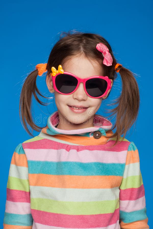 Portrait of an emotional girl of five years old in a striped sweater and in children`s glasses on a blue background stock images