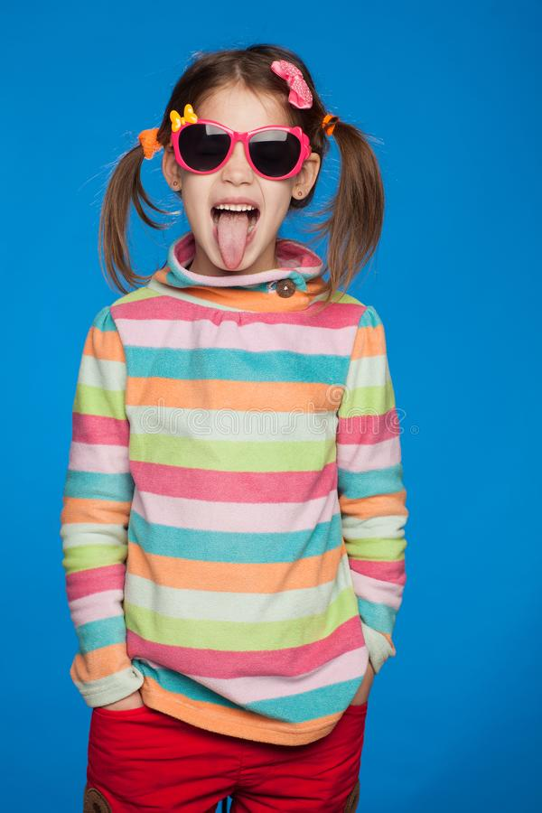 Portrait of an emotional girl of five years old in a striped sweater and in children`s glasses on a blue background stock photos