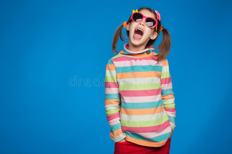 Portrait of an emotional girl of five years old in a striped sweater and in children`s glasses on a blue background royalty free stock photos