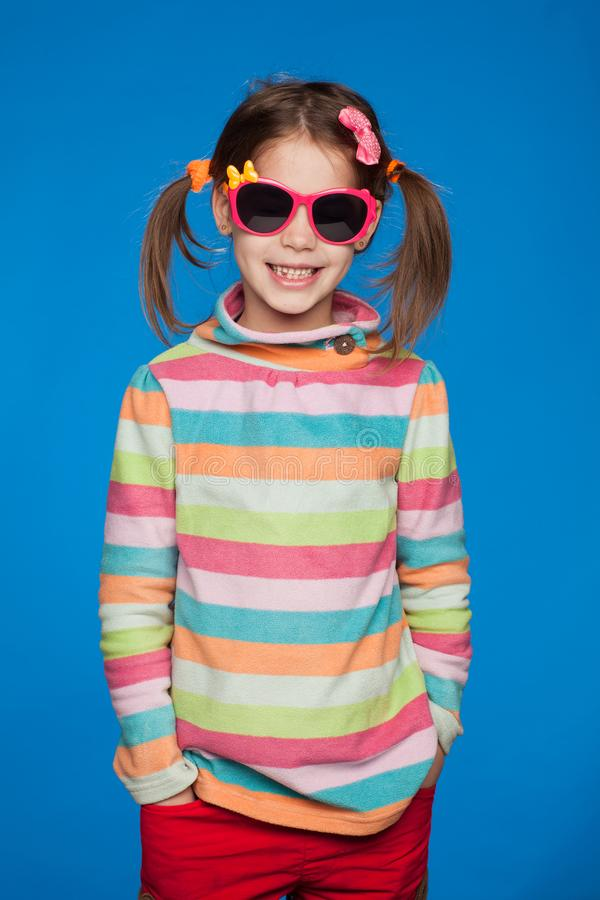 Portrait of an emotional girl of five years old in a striped sweater and in children`s glasses on a blue background royalty free stock images