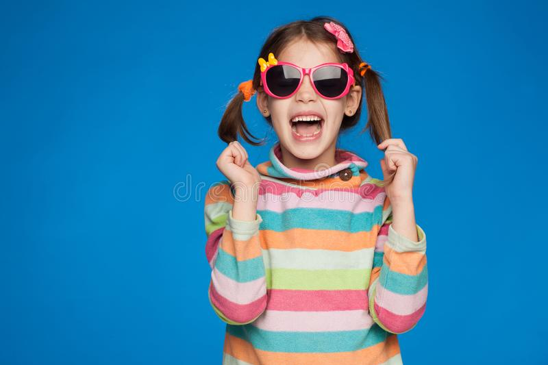Portrait of an emotional girl of five years old in a striped sweater and in children`s glasses on a blue background royalty free stock photography