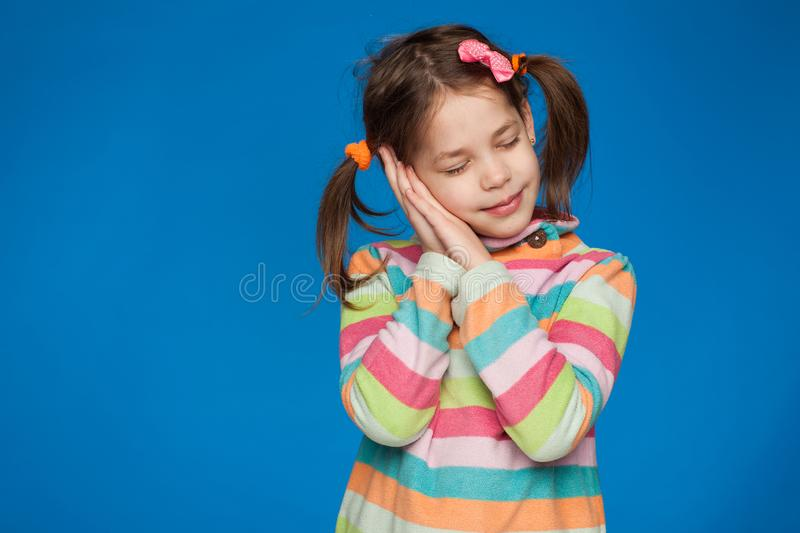 Portrait of an emotional girl of five years in a striped sweater on a blue background stock images