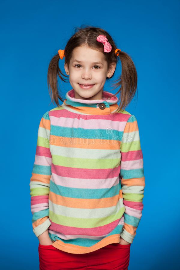 Portrait of an emotional girl of five years in a striped sweater on a blue background royalty free stock photography