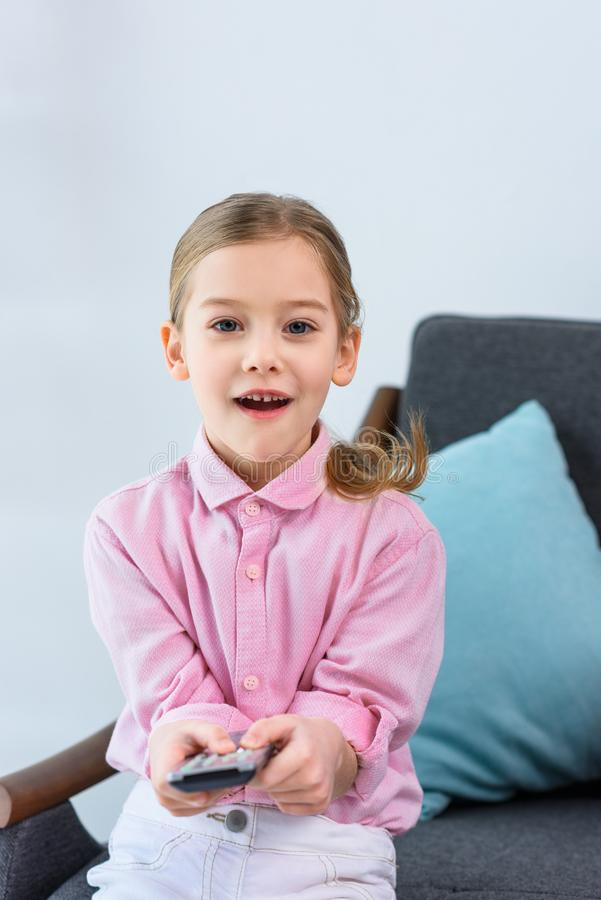 portrait of emotional kid with remote control sitting on sofa stock image