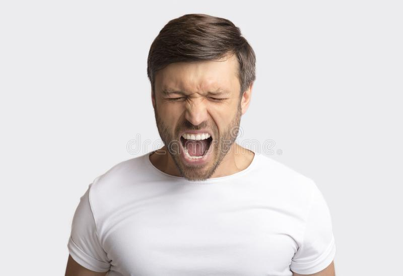 Portrait Of Emotional Man Screaming Furiously Over White Background. Anger Expression. Portrait Of Crazy Man Shouting Furiously Over White Studio Background stock photography