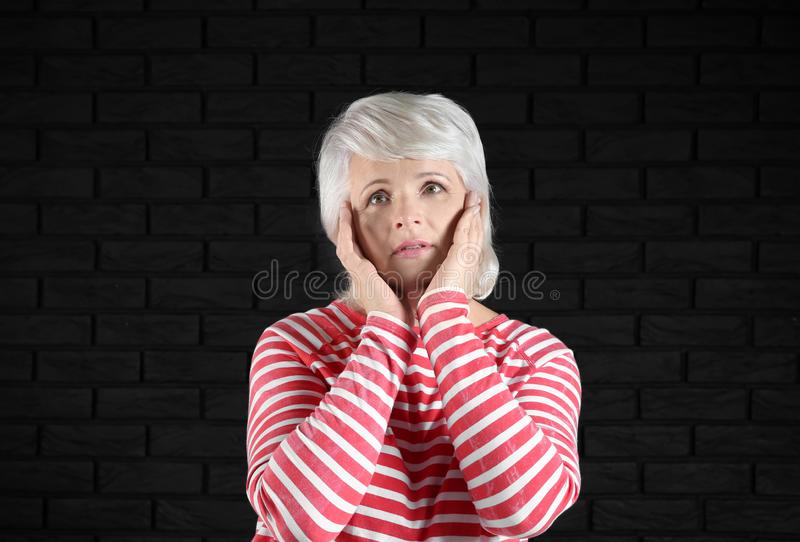 Portrait of emotional mature woman on dark background royalty free stock photography