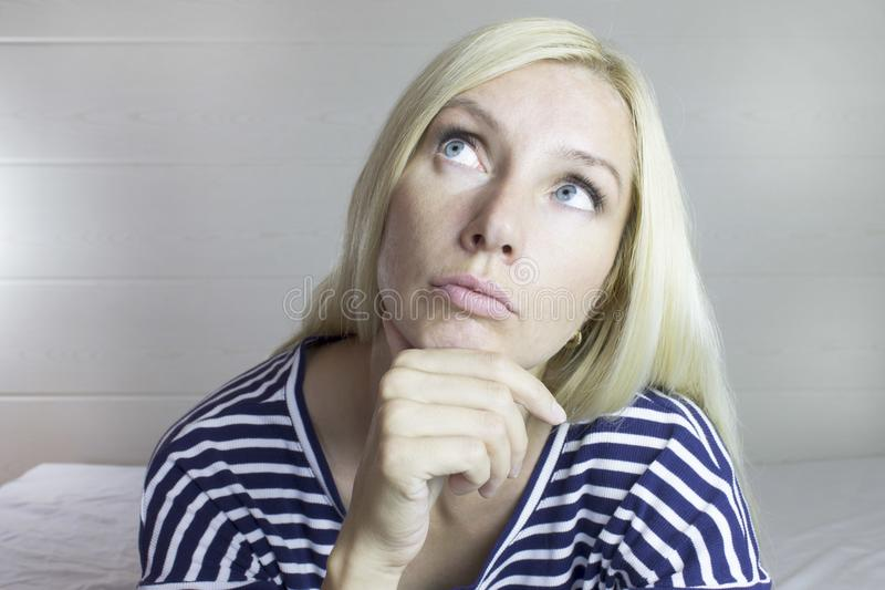 Portrait of emotional thoughtful beautiful cute blond woman, light gray background. Facial expressions. royalty free stock photo