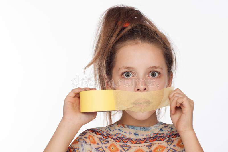 Portrait of an emotional 8-year-old girl, with her hair raised up and in a blouse with ornaments that glue paper tape on her mouth royalty free stock images