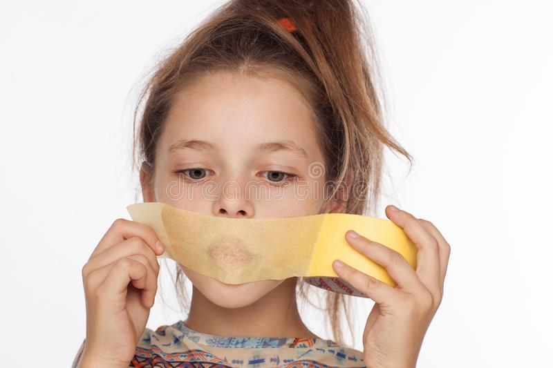 Portrait of an emotional 8-year-old girl, with her hair raised up and in a blouse with ornaments that glue paper tape on her mouth stock image