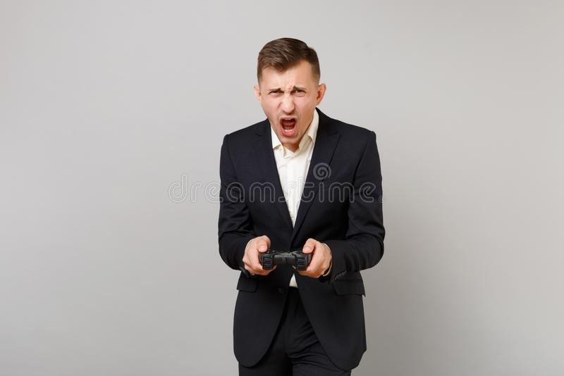 Portrait of emotional young business man in classic black suit, shirt playing video game with joystick isolated on grey royalty free stock image