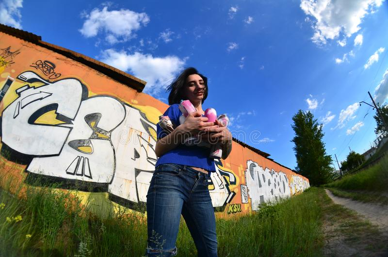 A wide-angle photo of a girl with aerosol paint cans in the hands on a graffiti wall background. Portrait of an emotional young girl with black hair and stock images