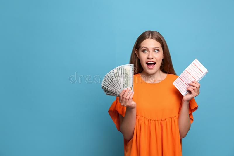 Portrait of emotional young woman with lottery ticket and money fan on light blue background royalty free stock photo