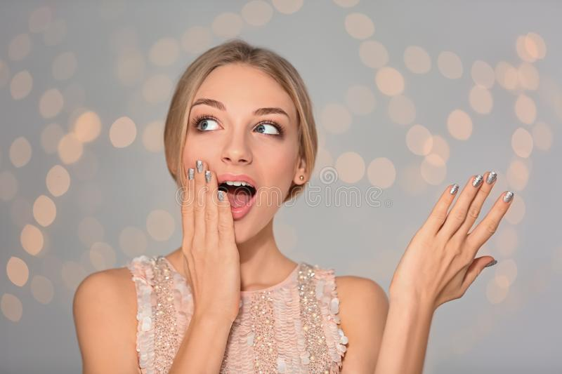 Portrait of emotional young woman with shiny manicure on blurred background royalty free stock photo