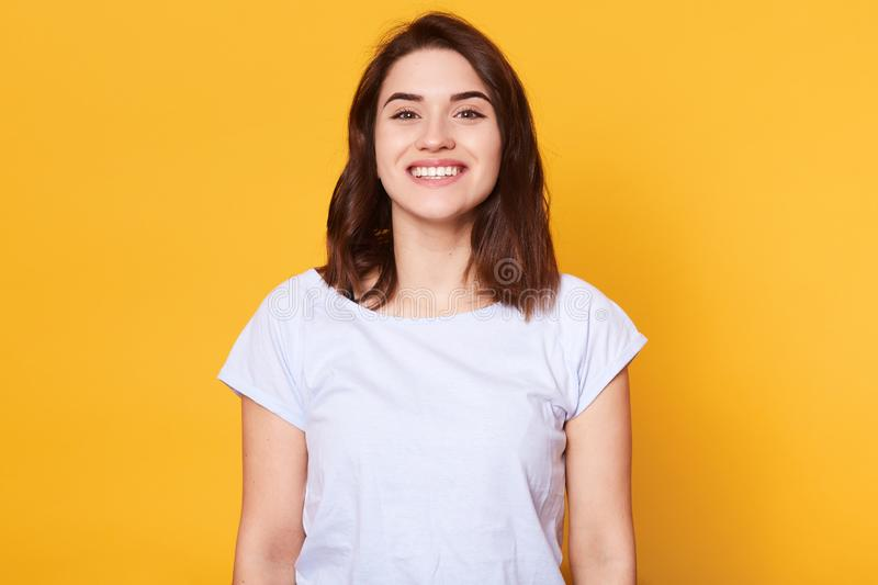 Portrait of emotive good looking caucasian woman laughs while looking directly at camera and standing against yellow background. royalty free stock photography