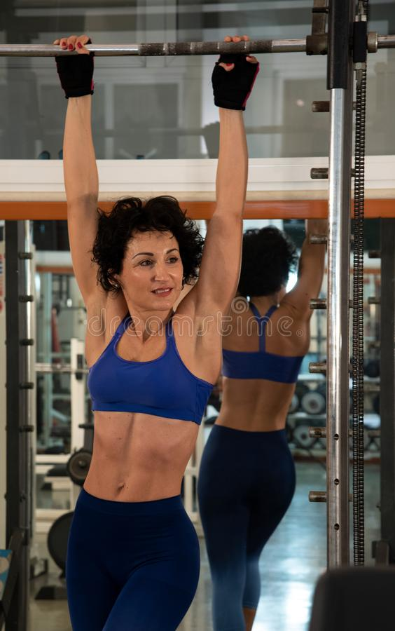 Portrait en buste d'une jeune fille musculaire avec un corsage bleu, elle emploie le multipower dans le gymnase image stock