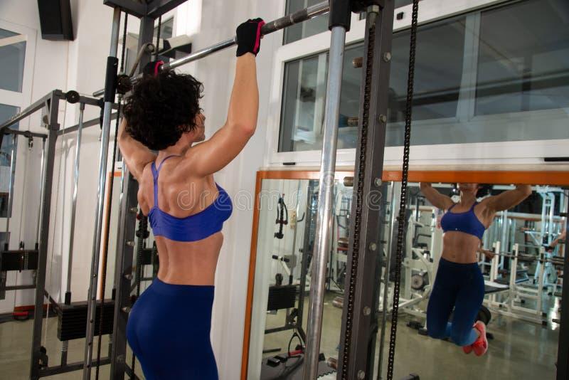 Portrait en buste d'une jeune fille musculaire avec un corsage bleu, elle emploie le multipower dans le gymnase photographie stock