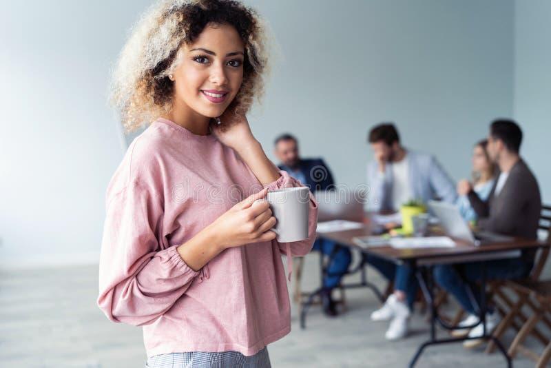 Portrait en buste de café appréciant femelle africain dans le bureau, jeune femme gaie d'affaires satisfaite de réussi photo stock