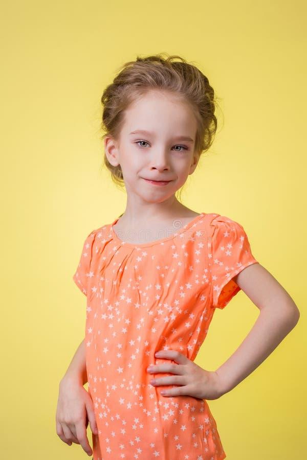 Portrait en buste de fille de l'adolescence heureuse d'isolement sur le fond jaune photos stock