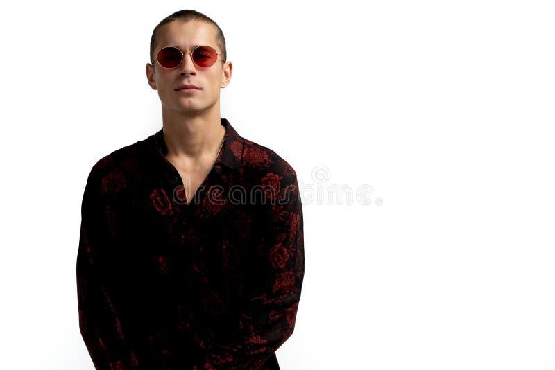 Portrait en buste de jeune enterpreneur masculin s?r et r?ussi dans la chemise noire et des lunettes de soleil rouges, avec le sh photo libre de droits