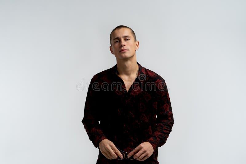 Portrait en buste de jeune homme attirant avec la coiffure courte, chemise ? la mode de port, tenant des lunettes de soleil dans  photographie stock