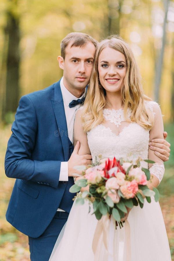Portrait en buste du marié étreignant la jeune mariée avec le dos de bouquet de mariage Composition d'automne images libres de droits