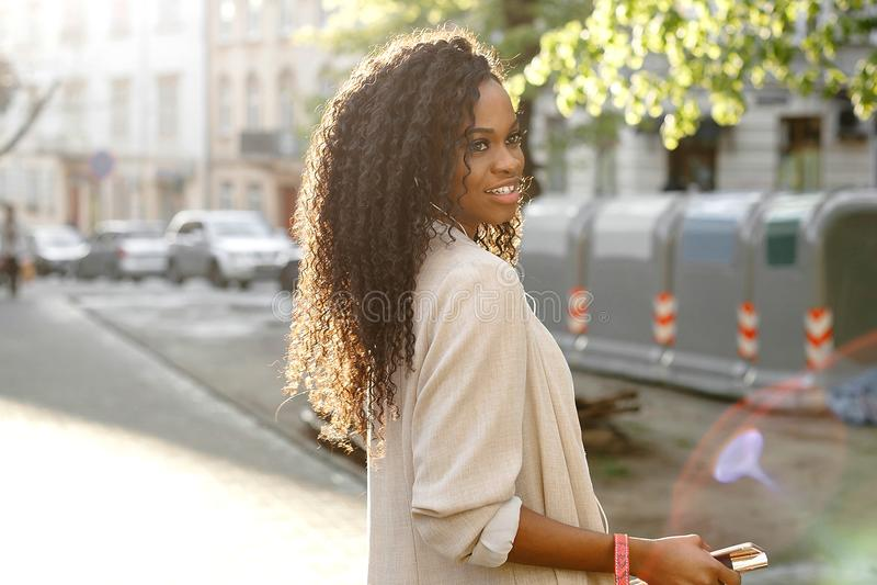 Portrait en buste latéral de la jeune belle fille africaine avec les cheveux bouclés et le sourire avec du charme regardant de cô images libres de droits