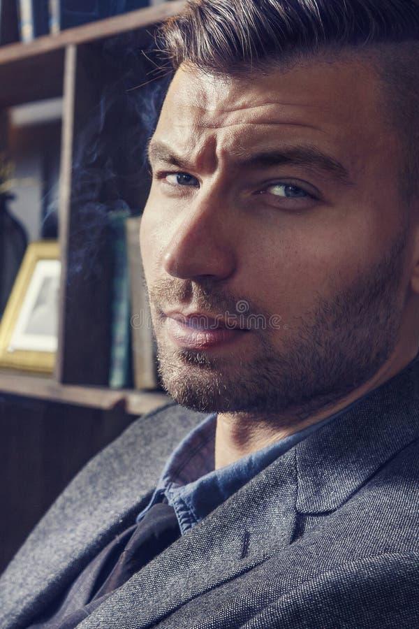 Portrait en gros plan d'homme réussi et sûr élégant avec la coiffure à la mode fumant dans la maison image stock