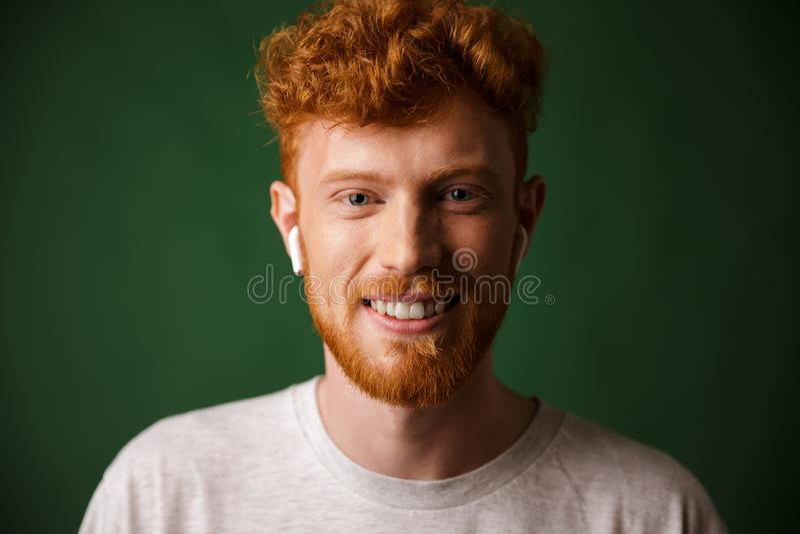 Portrait en gros plan d'homme roux bouclé de sourire, écoutant le mus photos libres de droits