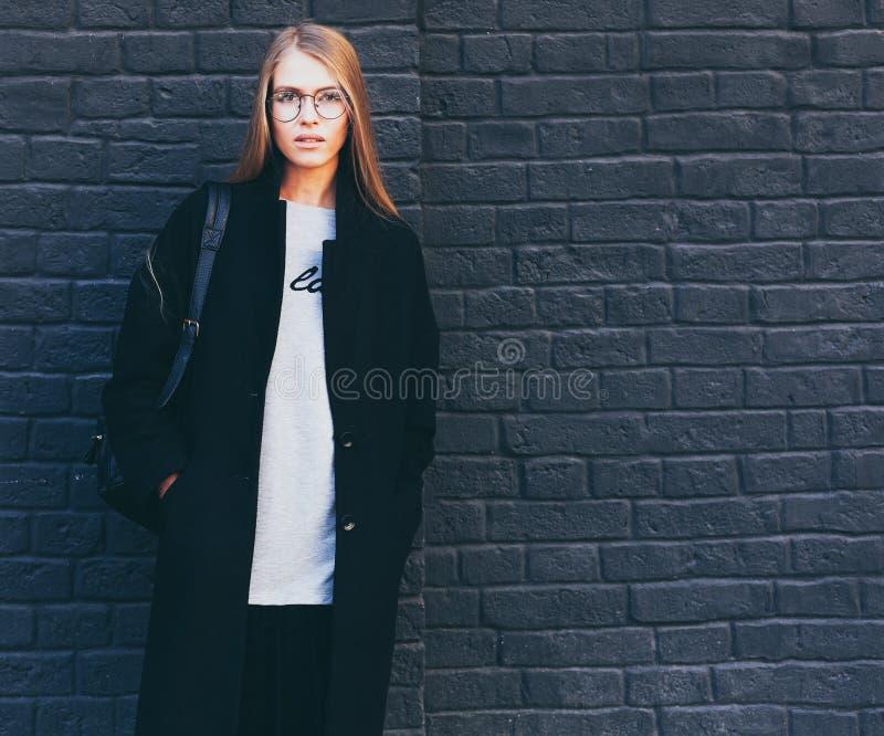 Portrait en gros plan d'une belle fille blonde dans les verres à la mode ronds dans un manteau noir et les bottes près d'une briq images libres de droits