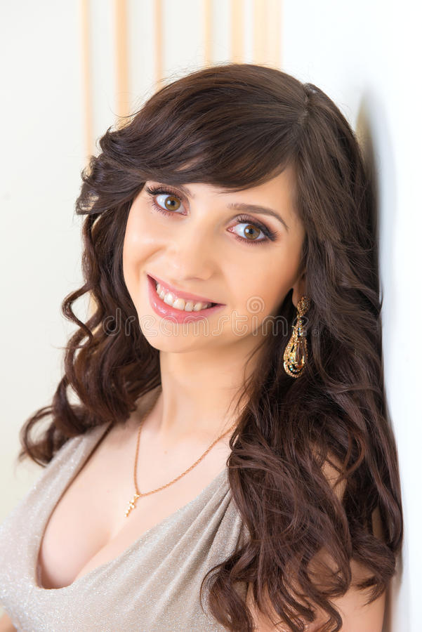 Portrait en gros plan d'une belle fille dans une robe d'or avec une encolure photo stock