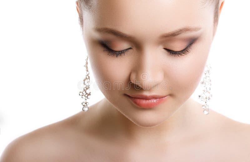 Portrait en gros plan d'une jeune fille avec un maquillage de mariage Peau parfaite, cheveux lisses, grandes boucles d'oreille en images libres de droits