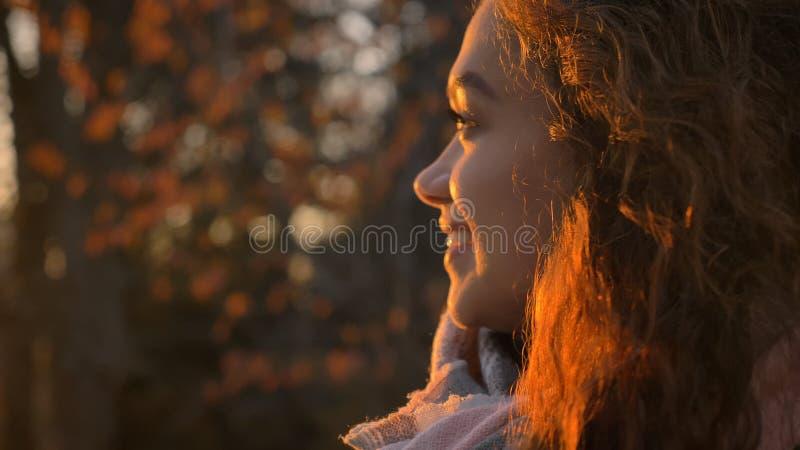 Portrait en gros plan dans le profil de la fille caucasienne aux cheveux bouclés observant de côté joyeux en parc automnal photo stock
