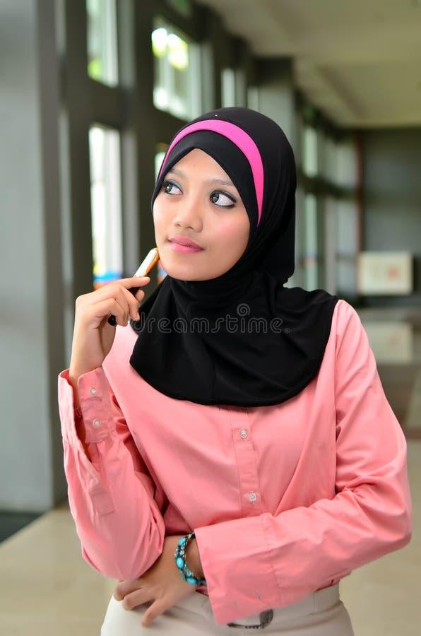 Portrait en gros plan de beau jeune stylo de participation asiatique de femmes d'affaires image stock